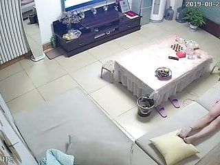 Beautiful Chinese girl lying on the couch watching TV and masturbating